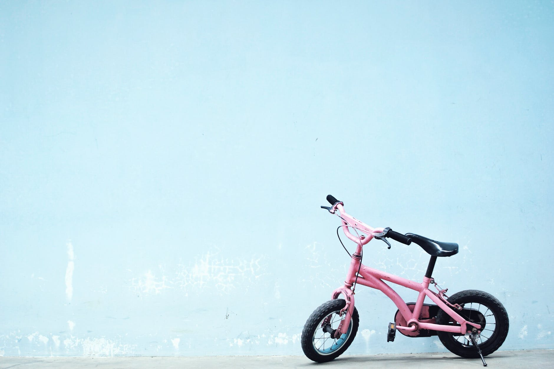 toddler s pink bike near wall