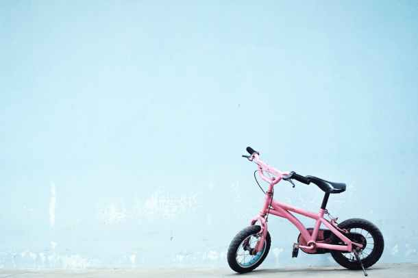 toddler s pink bike near wall